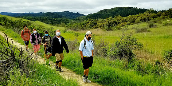 family hiking wearing face masks for safe social distancing