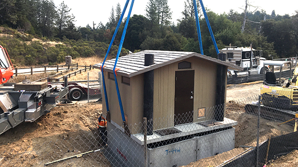 a crane moving a modular restroom into place