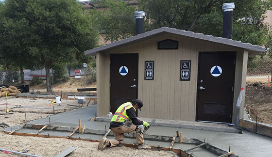 A worker smooths cement in front of a newly installed restroom